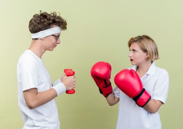 Młody sportowy para mężczyzna z hantlami, patrząc na swoją dziewczynę z rękawic bokserskich, uśmiechając się nad światłem