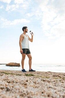 Młody sportowy sportowiec odpoczywa po joggingu na plaży i pije wodę