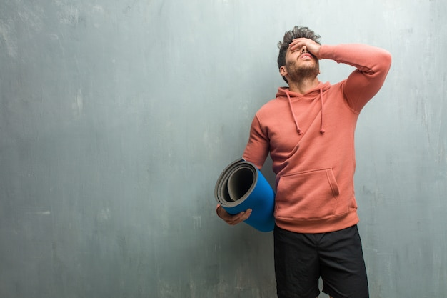 Młody sprawność fizyczna mężczyzna przeciw grunge ścianie udaremniającej i desperackiej, gniewnej i smutnej z rękami na głowie.