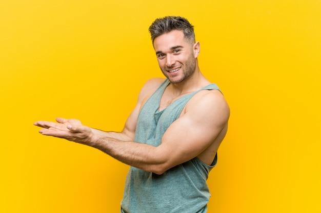 Młody sprawność fizyczna mężczyzna przeciw yellow trzyma a na palmie.