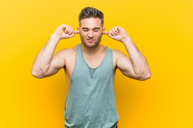 Młody sprawność fizyczna mężczyzna przeciw żółtej ścianie zakrywa ucho z rękami.