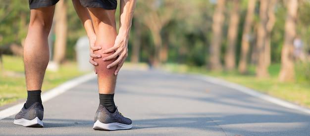 Młody sprawność fizyczna mężczyzna trzyma jego sport nogi uraz. mięsień bolesny podczas treningu
