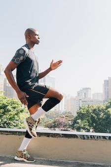 Młody sprawności fizycznej kobiety biegacz rozgrzewkowy up przed biegać na dachu