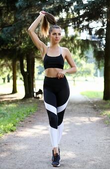 Młody sprawności fizycznej kobiety portret przeciw plenerowemu parkowemu tłu