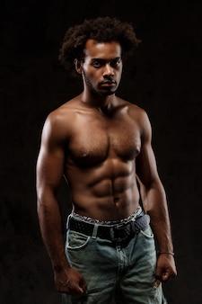 Młody sprawny afrykański mężczyzna pozuje nad czerni ścianą.