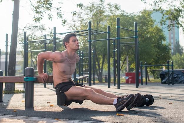 Młody sprawny człowiek robi triceps zanurza ćwiczenia podczas treningu na świeżym powietrzu trening krzyżowy. fitness model męski.