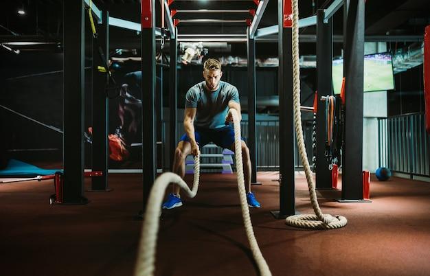 Młody sprawny mężczyzna ćwiczący z linami bojowymi na siłowni