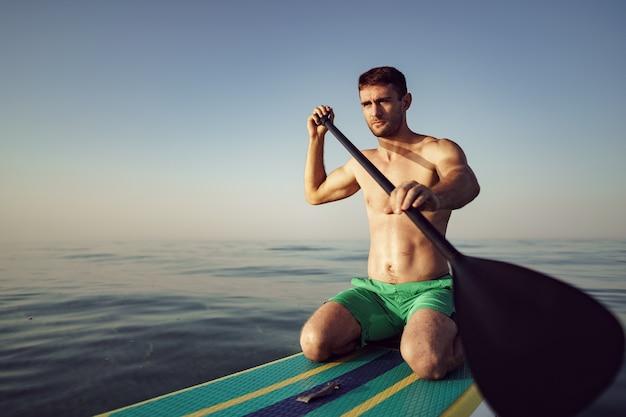 Młody sprawny mężczyzna na desce wiosłowej unoszącej się na jeziorze o wschodzie słońca