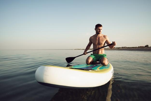 Młody sprawny mężczyzna na desce wiosłowej unoszącej się na jeziorze