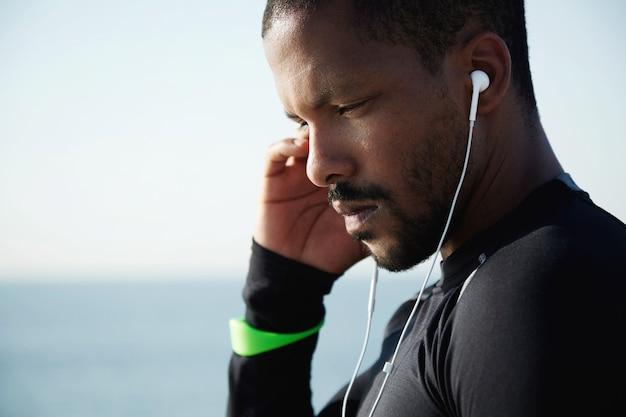 Młody sprawny mężczyzna na plaży, słuchanie muzyki