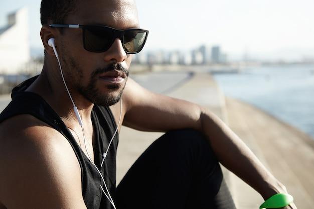 Młody sprawny mężczyzna na plaży w okularach przeciwsłonecznych