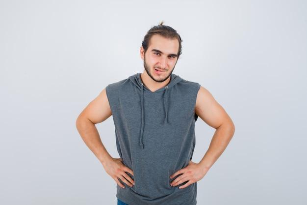 Młody sprawny mężczyzna pozuje z rękami w talii w bluzie bez rękawów i wygląda zamyślony. przedni widok.