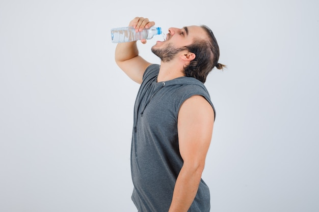Młody sprawny mężczyzna w bez rękawów bluza z kapturem pijącej wodę i wyglądający wesoło, widok z przodu.