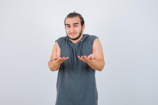 Młody sprawny mężczyzna w bluzie bez rękawów, robiący gest pytający i wyglądający na przygnębionego, widok z przodu.