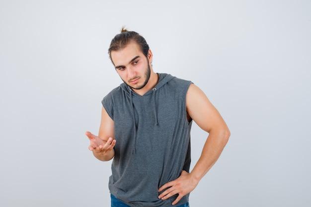 Młody sprawny mężczyzna w bluzie bez rękawów wyciągającej rękę w kierunku aparatu i wyglądającego zamyślnie, w widoku z przodu.