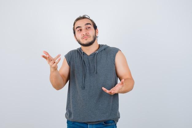 Młody sprawny mężczyzna w bluzie bez rękawów, wyciągający dłoń w pytający sposób i wyglądający na zamyślonego, widok z przodu.