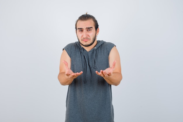 Młody sprawny mężczyzna w bluzie bez rękawów z bezradnym gestem i zrzędliwym spojrzeniem z przodu.