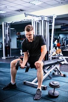 Młody sprawny mężczyzna w sportowej, podnosząc ciężary i pracując na bicepsach w siłowni