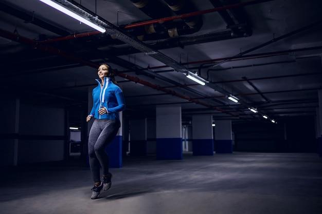 Młody sprawny sportowiec kaukaski w dresie biegnie szybko w garażu.