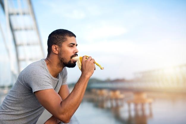 Młody sprawny sportowy człowiek jedzenie banana i uśmiechnięty