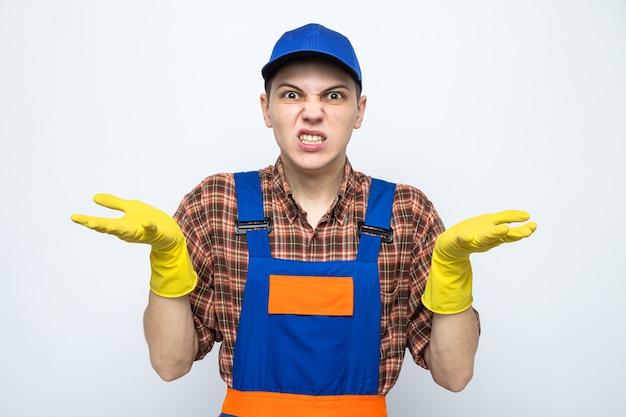 Młody sprzątacz ubrany w mundur i czapkę z rękawiczkami na białym tle na białej ścianie