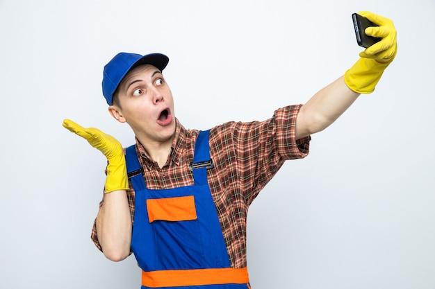 Młody sprzątacz ubrany w mundur i czapkę z rękawiczkami robi selfie na białym tle na białej ścianie