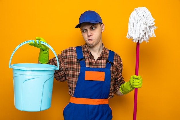 Młody sprzątacz ubrany w mundur i czapkę z rękawiczkami, trzymający mopa i wiadro na białym tle na pomarańczowej ścianie