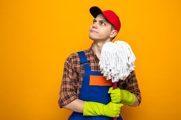 Młody sprzątacz ubrany w mundur i czapkę z rękawiczkami, trzymający mopa na pomarańczowej ścianie