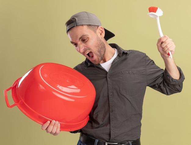 Młody sprzątacz ubrany w ubranie i czapkę trzymając umywalkę i szczotka do czyszczenia krzycząc z agresywnym wyrazem stojącym nad zieloną ścianą