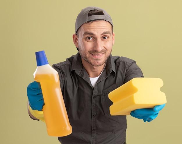 Młody sprzątacz ubrany w ubranie i czapkę w gumowych rękawiczkach, trzymając butelkę ze środkami czyszczącymi i gąbką, patrząc uśmiechnięty stojący nad zieloną ścianą