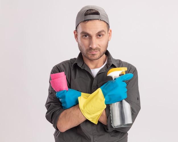Młody sprzątacz ubrany w ubranie i czapkę w gumowych rękawiczkach, trzymając spray do czyszczenia i szmatę, patrząc z poważną twarzą stojącą nad pomarańczową ścianą