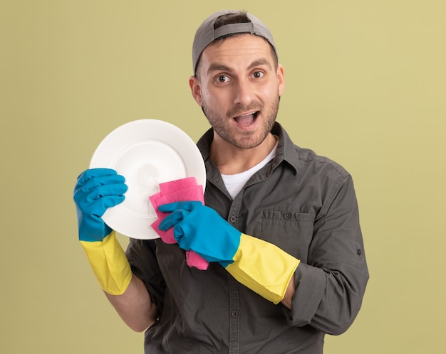 Młody sprzątacz ubrany w ubranie i czapkę w gumowych rękawiczkach, trzymając talerz i szmatę, patrząc szczęśliwy i podekscytowany stojąc nad zieloną ścianą
