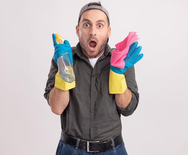Młody sprzątacz ubrany w zwykłe ubranie i czapkę w gumowych rękawiczkach, trzymając butelkę z rozpylaczem i szmatkę, patrząc zdziwiony i zaskoczony stojąc nad białą ścianą