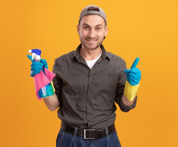 Młody sprzątacz ubrany w zwykłe ubranie i czapkę w gumowych rękawiczkach trzymający butelkę z rozpylaczem i szmatkę, uśmiechnięty radośnie, pokazujący kciuki w górę stojąc nad pomarańczową ścianą