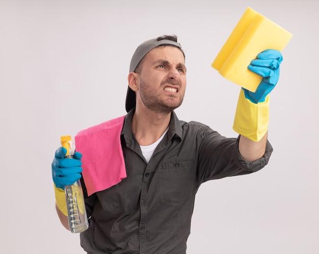 Młody sprzątacz ubrany w zwykłe ubranie i czapkę w gumowych rękawiczkach trzymający spray do czyszczenia i gąbkę ze szmatą na ramieniu, patrząc na gąbkę z zirytowaną miną stojącą nad pomarańczową ścianą