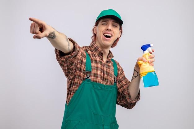 Młody sprzątacz w kombinezonie koszulowym w kratę i czapce, trzymając szmatkę i spray do czyszczenia szczęśliwy i wesoły, wskazując palcem wskazującym na coś szeroko uśmiechniętego