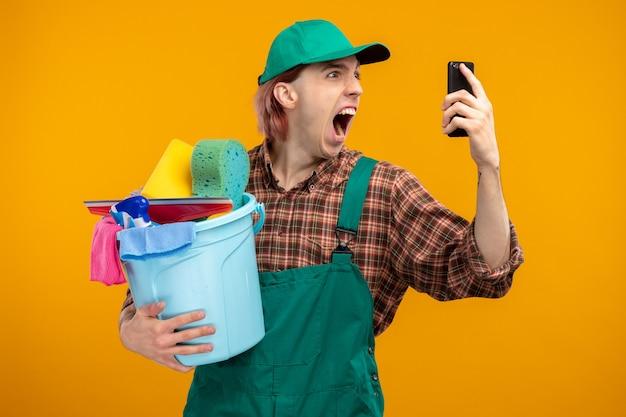 Młody sprzątacz w kombinezonie w kratę i czapce trzymającej wiadro z narzędziami do czyszczenia krzyczący z agresywną miną podczas rozmowy na telefonie komórkowym stojącym na pomarańczowo