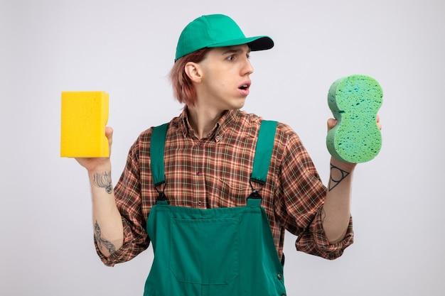 Młody sprzątacz w kombinezonie w kratę i czapce, trzymający gąbki, wyglądający na zdezorientowanego, próbujący dokonać wyboru stojąc na białym tle
