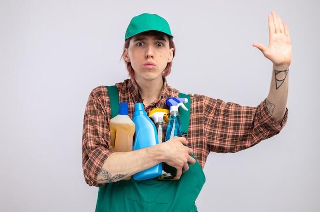 Młody sprzątacz w kombinezonie w kratę i czapce trzymający środki czystości martwi się podnoszeniem ręki stojącej nad białą ścianą