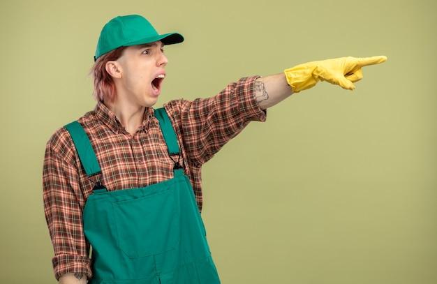 Młody sprzątacz w kombinezonie w kratę i czapce w gumowych rękawiczkach, patrząc na bok, krzycząc z mylącym wyrazem wskazującym na coś palcem wskazującym