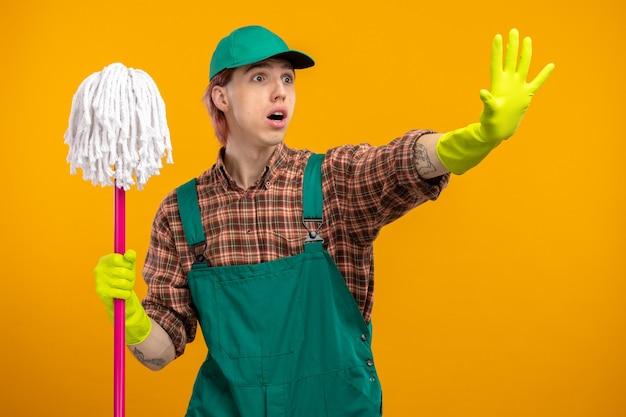 Młody sprzątacz w kombinezonie w kratę i czapce w gumowych rękawiczkach, trzymając mopa, patrząc na bok, zmartwiony, wykonując gest zatrzymania
