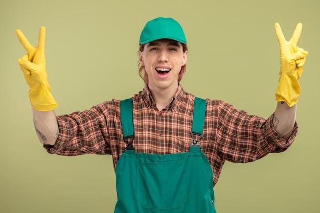 Młody sprzątacz w kombinezonie w kratę i czapce w gumowych rękawiczkach, uśmiechnięty radośnie, szczęśliwy i pozytywny pokazując znak v