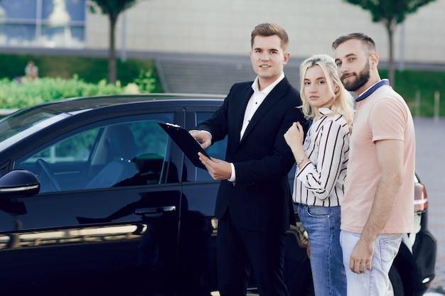 Młody sprzedawca pokazuje klientom nowy samochód. mężczyzna i kobieta kupują samochód.
