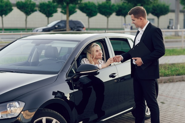 Młody sprzedawca pokazuje klientom nowy samochód. szczęśliwa kobieta kupuje nowy samochód. młoda kobieta siedzi za kierownicą, sprzedawca daje jej kluczyki.