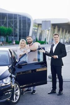 Młody sprzedawca pokazuje klientom nowy samochód. szczęśliwa młoda para, mężczyzna i kobieta kupują nowy samochód