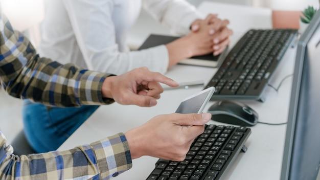 Młody startup programiści siedzący przy biurkach ekran pracujący nad komputerami do programowania i kodowania w celu znalezienia rozwiązania problemu w nowej aplikacji
