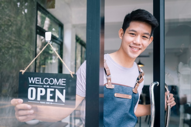 Młody startupowy właściciel kawiarni z kawą otwarty i mile widziany klient.