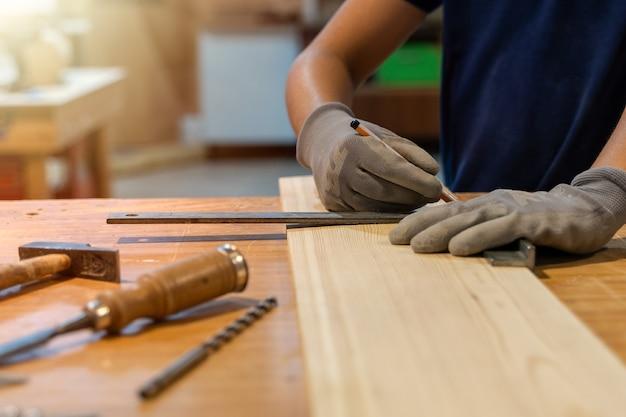 Młody stolarz mierzący drewno linijką.
