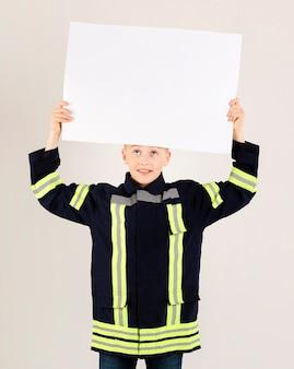 Młody strażak gospodarstwa pusty transparent