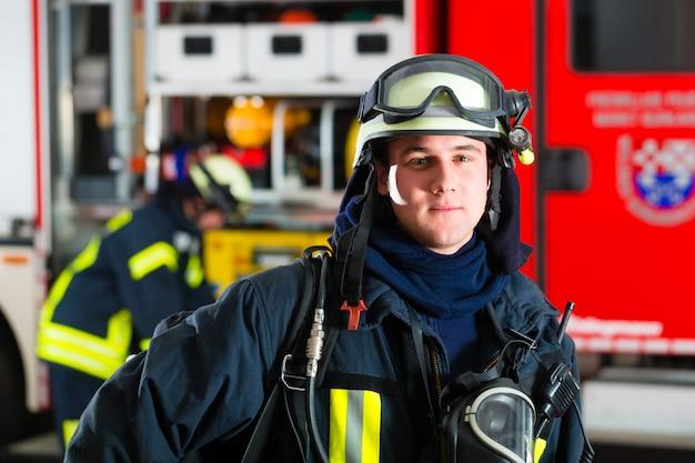 Młody strażak w mundurze przed wozem strażackim